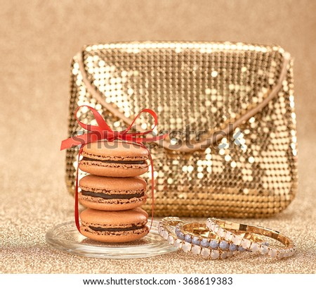 Fashion woman essentials set. Luxury Gold handbag and Macarons. Ladies Fashionable glamor gold clutch. Elegant fashion style.Creative party Outfit, fashion shiny Accessories, golden background.Vintage