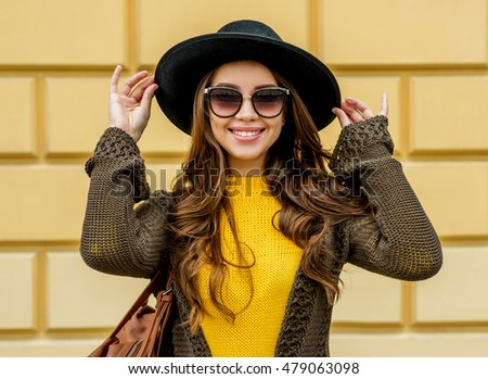 Fashion woman in a hat and sunglasses, in knit dress and jacket outdoors in the fall. Autumn time.