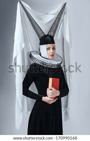 Fashion woman in a medieval gothic style clothing against studio background - stock photo