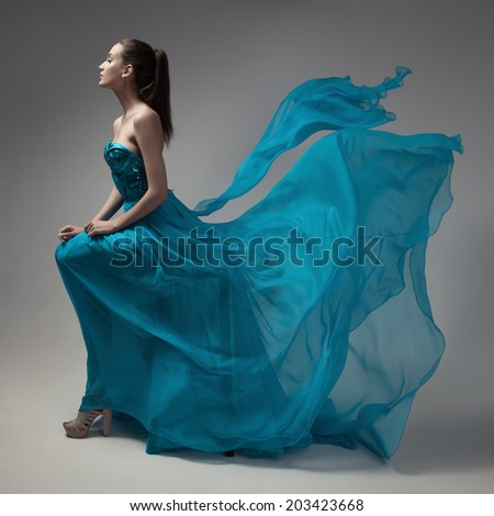 Fashion woman in fluttering blue dress. Gray background. - stock photo