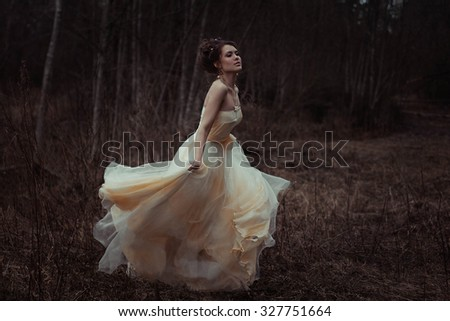 Fashion woman in forest in amazing dress