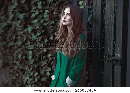 Fashion woman in green coat posing outdoors - stock photo