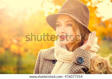 Fashion Woman in Hat and Scarf on Yellow Autumn Background in Sunny Day. Girl Portrait. Toned Photo with Bokeh and Copy Space.