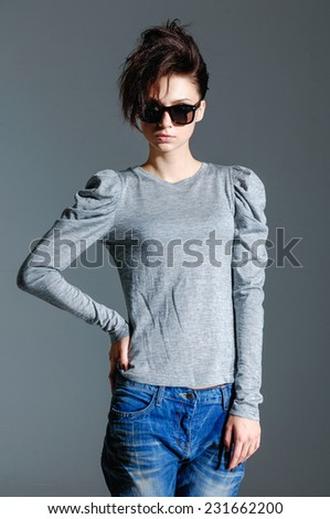 fashion woman in jeans with sunglasses on gray  - stock photo