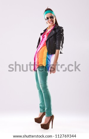 fashion woman in leather jacket and high heels making funny faces and exposing her tongue - stock photo