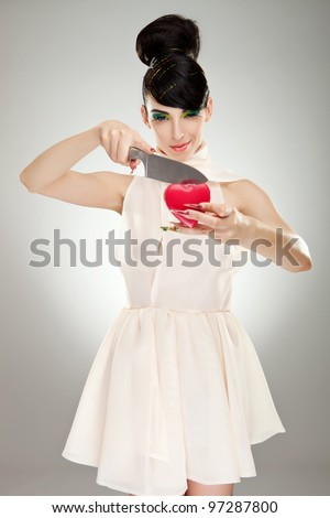 fashion woman in nice dress with colorful makeup and big finger nails, cutting a heart with a big kitchen knife - stock photo