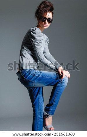 fashion woman in sunglasses with jeans on gray background - stock photo