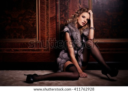 Fashion woman in underwear and fur coat sitting on the floor in antique room.