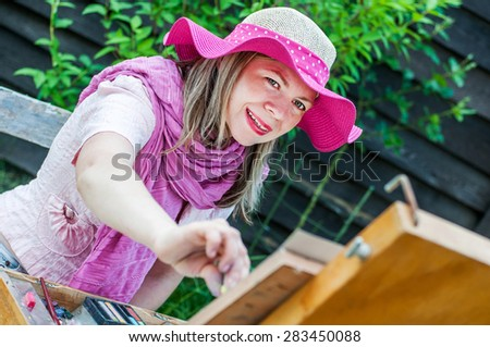 Fashion woman is painting. Open air session - stock photo