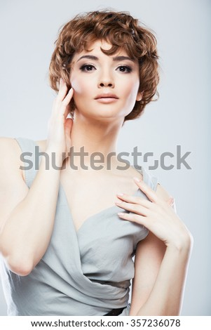Fashion woman model posing in snapshot style at studio against gray isolated background.