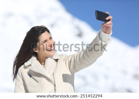 Fashion woman photographing a selfie in winter holidays with a snowy mountain in the background - stock photo