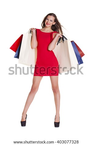 Fashion woman portrait isolated. White background. Happy girl hold shopping bags. Red dress. female beautiful model - stock photo