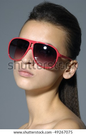 fashion woman portrait wearing sunglasses over a gray