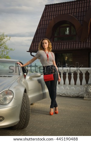 Fashion woman posing near luxury car