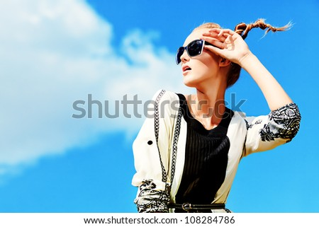 Fashion woman posing over blue sky.