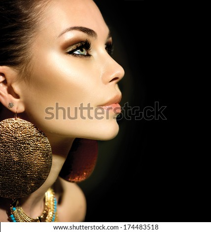 Fashion Woman Profile Portrait isolated on black. Golden Jewels. Trendy Makeup. Smoky eyes make up. Gold Jewellery. Accessories  - stock photo