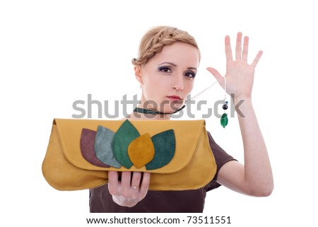 fashion woman pulling her necklace and showing a nice purse to the camera - stock photo
