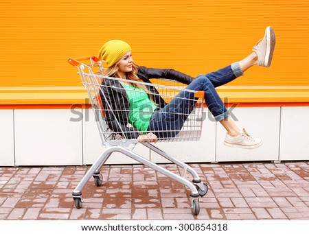 Fashion woman riding having fun in shopping trolley cart over colorful urban background - stock photo