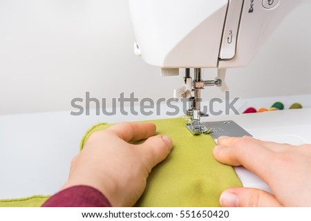 Fashion woman sews with sewing machine - sewing concept