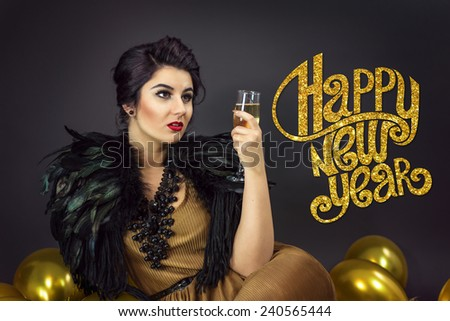 Fashion woman sitting ,drinking champagne, dressed in a gold dress and feathers collar, surrounded with yellow balloons . Happy new year copy text on the left - stock photo