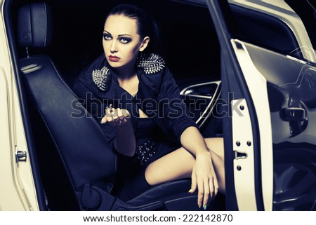 Fashion woman smoking cigarette in a car  - stock photo