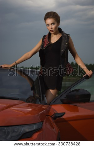 Fashion  woman standing near vehicle with opened door. Low key - stock photo