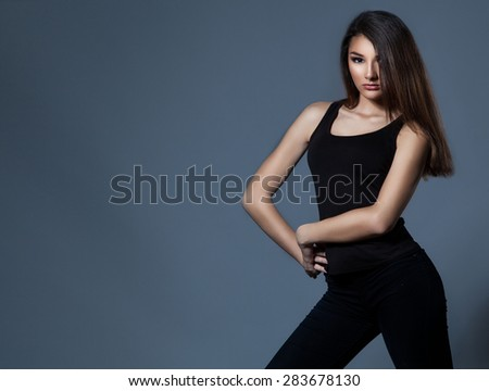 Fashion woman standing over grey background in black clothes. - stock photo