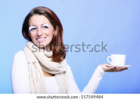 Fashion woman stylish winter makeup holding cup of hot drink beverage enjoying coffee time copyspace blue background - stock photo