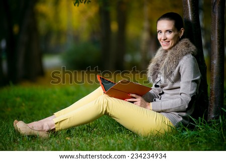 Fashion woman using a tablet computer outside in evening park. Student sitting on green grass over tree. - stock photo