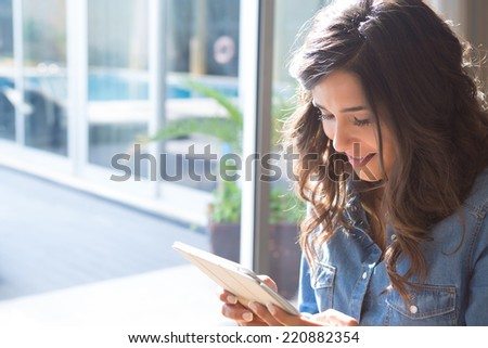 Fashion woman using tablet with sunbeams and lens flare - stock photo
