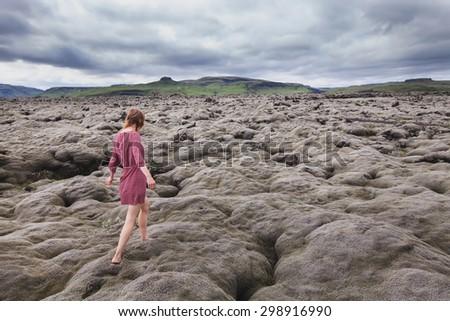 fashion woman walking barefoot in lava field in Iceland - stock photo