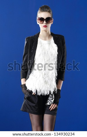 fashion woman wearing sunglasses against blue background - stock photo