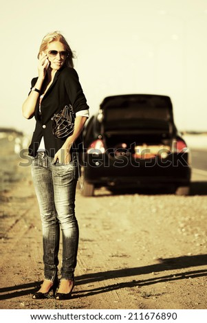 Fashion woman with broken car calling on the cell phone  - stock photo