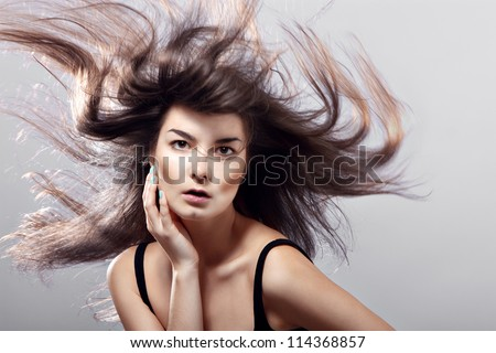 fashion woman with flying hair on a gray background.