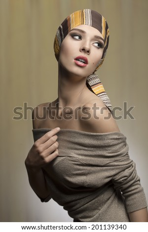 fashion woman with foulard on the head in sensual pose with naked shoulders and brown dress