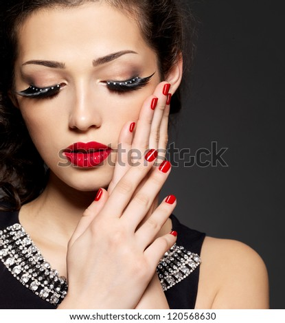 Fashion woman with modern creative makeup using false eyelashes red manicure - stock photo