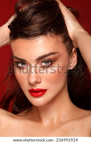 Fashion woman with red lips and smoky eyes, evening make up. Beauty. Portrait. Red background, studio shot. Perfect skin. Brunette. - stock photo