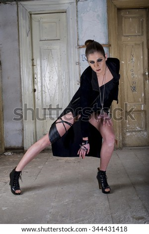 Fashion women posing at old dirty house in black dress and shoes