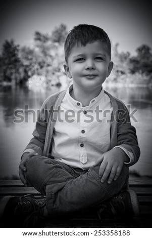 Fashion 3 years old kid. Handsome boy smiling at the camera, sitting cross-legged near the lake.. Outdoor picture. Black & white picture. - stock photo