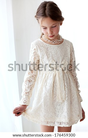 Fashion 7 years old model dressed in ivory lace dress pastel tone - stock photo