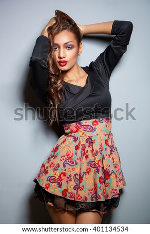 fashion young African woman with creative make-up and curly hair in short sexy dress isolated on gray - stock photo