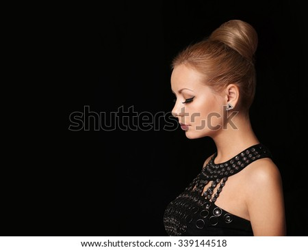 Fashion young beautiful girl with hair bun over black. Looking down