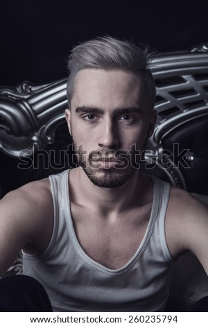 Fashion young blond male man with beard portrait in bedroom at night - stock photo