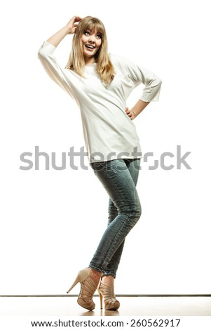Fashion. Young blonde woman denim pants white bat sleeve top high heels. Female model posing in full length isolated