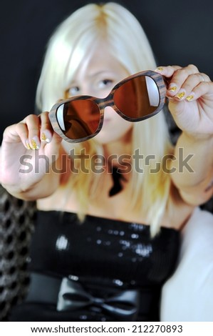 Fashion young blonde woman's hand holding wooden sunglasses on black background, focus on sunglasses