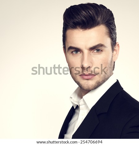 Fashion young businessman black suit casual  poses at studio - stock photo