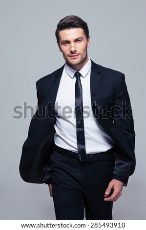 Fashion young businessman over gray background. Looking at camera - stock photo