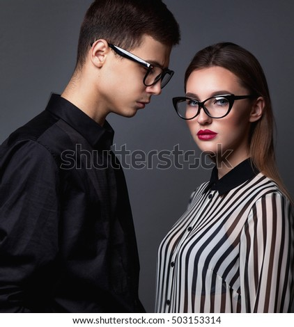 Fashion young couple in trendy glasses and stylish clothes over dark grey background.