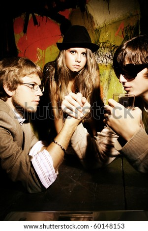 Fashion young guys and girls sitting together and having fun - stock photo