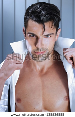 Fashion young man opening his shirt with sexy muscular chest - stock photo